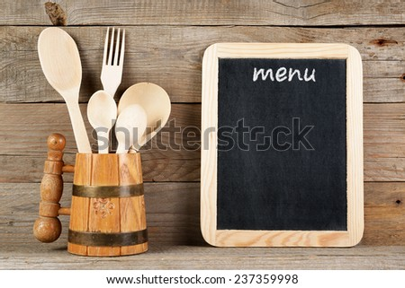 Menu board and wooden spoons and fork in mug - stock photo