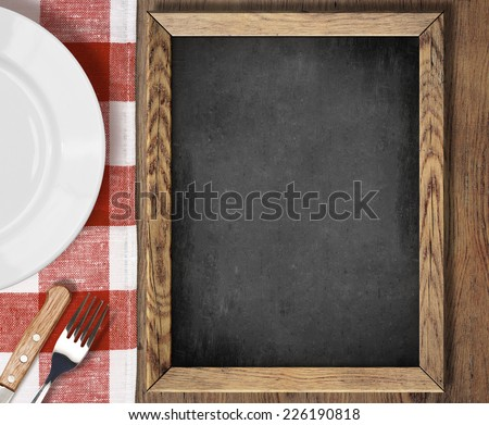 Menu chalkboard top view on table with plate, knife and fork - stock photo