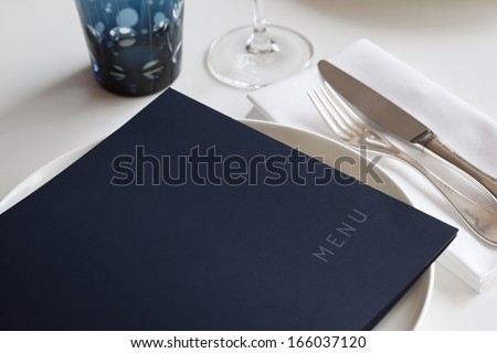 Menu on a table set in a restaurant - stock photo