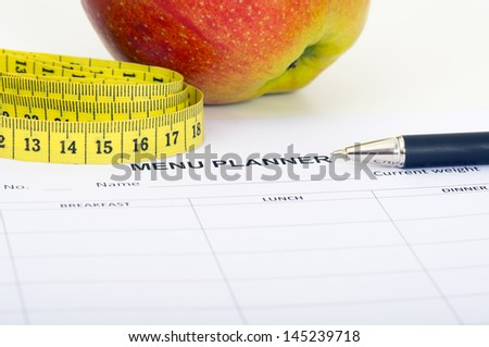 Menu planner with measuring tape and apple - stock photo