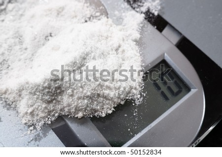 Mephedrone (aka meow, bubbles) powder on weighing scales - stock photo