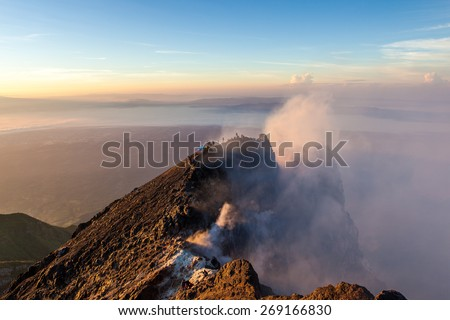 Merapi volcano crater rim with people at sunrise - stock photo