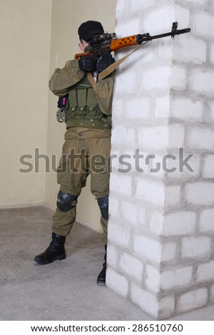mercenary sniper with sniper rifle inside the building  - stock photo
