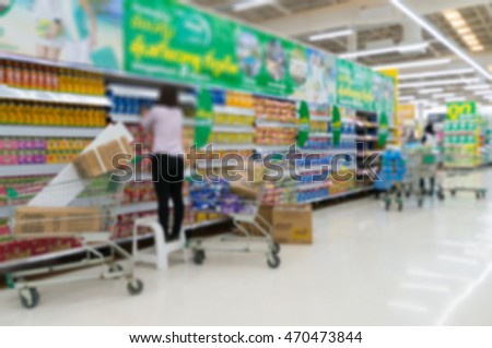 Merchandising. Sales assistant in supermarket arrange goods on supermarket shelves at store, Abstract Blur or Defocus Background
