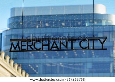 Merchant city sign at Royal Exchange Square Glasgow with new office building in background.
