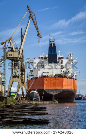 Merchant ship in the shipyard and the tiny boat next to him - stock photo
