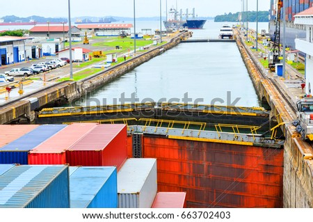 Merchant ships pass the locks of the Panama Canal. Container ship passes the Panama Canal
