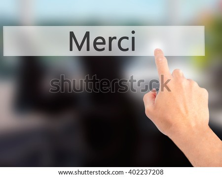 Merci - Hand pressing a button on blurred background concept . Business, technology, internet concept. Stock Photo