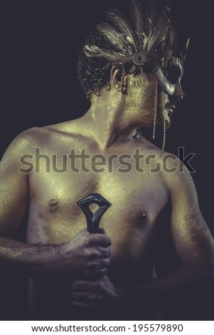 Mercury, Man with body painted gold feather mask and steel sword - stock photo