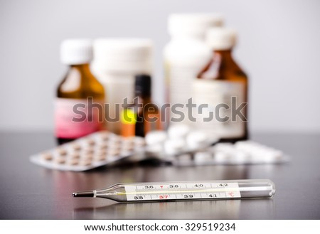 Mercury thermometer and medical pills on background - stock photo