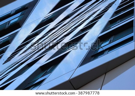 Merger between sky and reflecting semi-matte facade panels. Double exposure photo of contemporary building fragment. Abstract symmetrical architectural composition. - stock photo