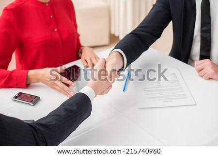 Merger. Three successful and confident businesspeople shake hands. Businesspeople in formal dress sitting in an office at a desk close-up view of hands