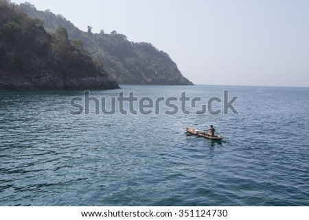 Mergui Archipelago, Myanmar - April 2015: a male Moken people rowing a fishing canoe on Andaman Sea. Moken people are known as Sea Gypsies who maintain nomadic life and a population of less than 3000.