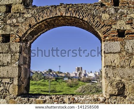 Merida, November 2012. Roman aqueduct ruins in Merida, capital of Extremadura region in Spain. I century. UNESCO World Heritage Site. Detail, Merida viewed throgh an arch. - stock photo