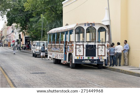 Merida, Yucatan Mexico, January 23, 2015: Passengers wait to board a guided tour bus on a city street in Merida Mexico. - stock photo