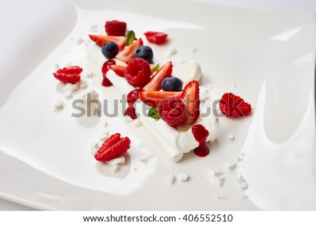 meringue cake decorated with fruit, strawberries, raspberries, blueberries. - stock photo