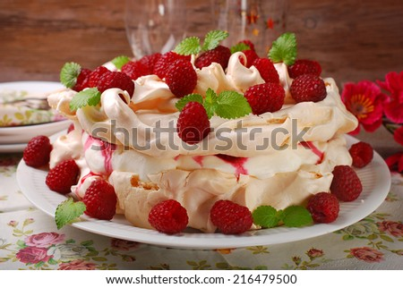 meringue  pavlova cake with whipped cream,caramel and fresh raspberries