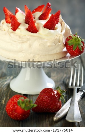 Meringue with whipped cream and strawberries on a white stand.
