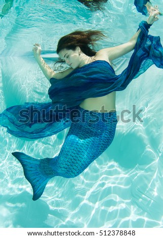Mermaid in blue, swimming in dappled sunlit pool.