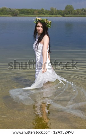 Mermaid in the water with a wreath on head - stock photo