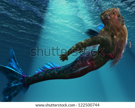 Mermaid of the Sea - Ocean light illuminates a magical mermaid as she swims up to the ocean surface. - stock photo