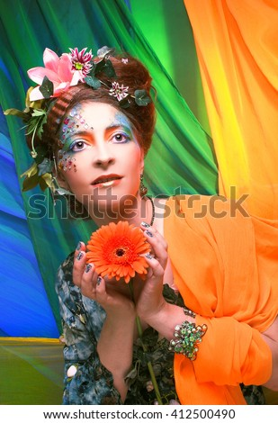 Mermaid. Portrait of young woman in creative image and with flowers.
