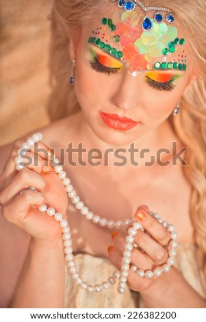 Mermaid portrait with pearls in hand - stock photo
