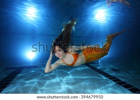 Mermaid swimming underwater in the pool  - stock photo