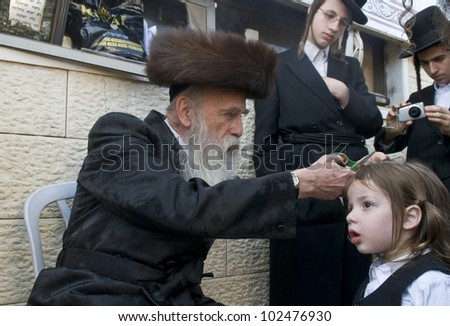 MERON , ISRAEL - MAY 10 : unidentified Rabbi cuts child's hair in a Halake ceremony in Bar Yochai tomb in Meron , Israel on May 10 2012 , Halake is first haircut ceremony celebrated in Lag Ba'omer - stock photo