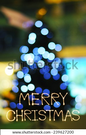 Merry Chirstmas sparkle fireworks with defocused lights on Christmas tree background - stock photo