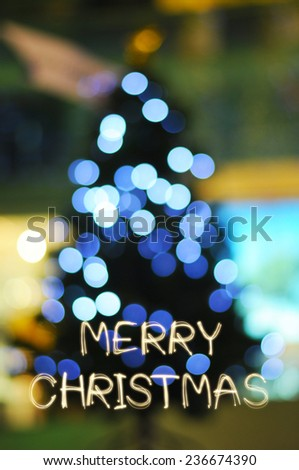 Merry Chirstmas sparkle text with defocused light on Christmas tree - stock photo