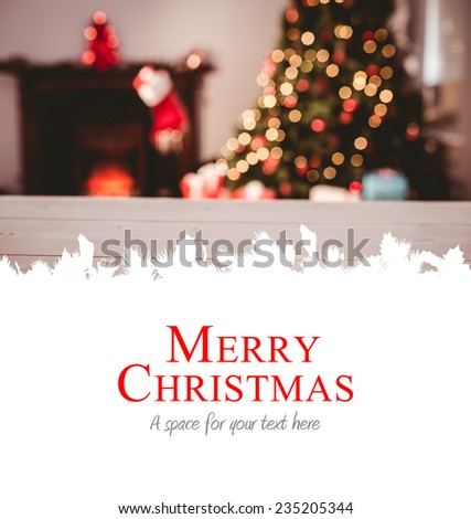 Merry christmas against desk with christmas tree in background - stock photo