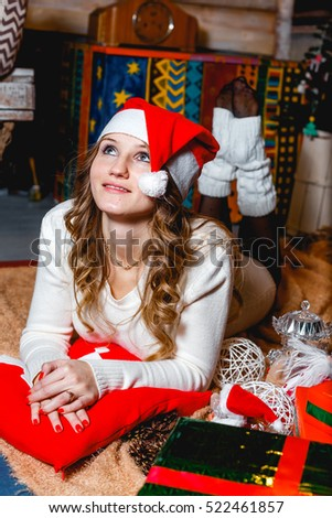 Merry Christmas and Happy Holidays! Beautiful blonde girl in santa hat lying and daydreaming.