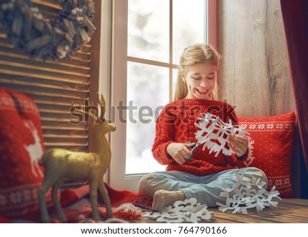 Merry Christmas and happy holidays! Cute little girl sitting by the window and making paper snow-flakes. Room decorated. Kid enjoys the snowfall.