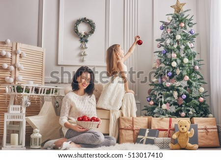 Merry Christmas and Happy Holidays!  Mom and daughter decorate the Christmas tree in room. Loving family indoors.