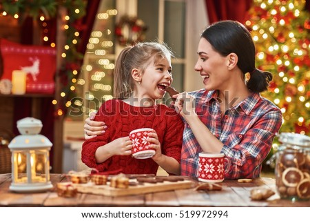 Merry Christmas and Happy Holidays. Time of family tea party. Mother and her child daughter are drinking warm tea with Christmas cookies.