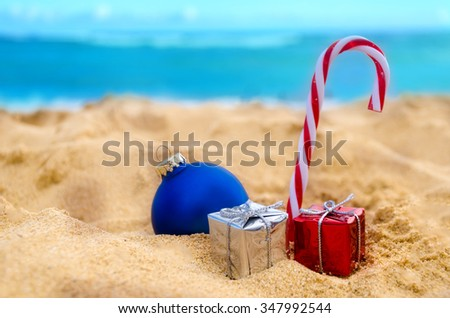 Merry Christmas and Happy New Year background, Christmas ball, candy and gifts on the tropical beach near ocean in Hawaii - stock photo