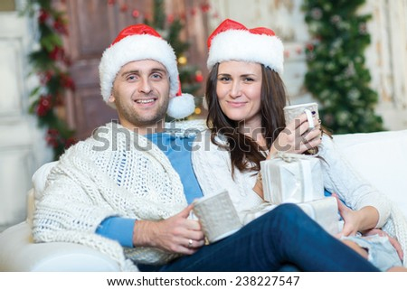 Merry Christmas and Happy New Year. Couple in love is sitting in festive Christmas decorated living room. Both are drinking New Year cacao from pretty Christmas cups and look in the camera