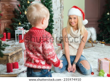Merry Christmas and Happy New Year. Ideal family Christmas, mother is sitting in festive New Year living room before Christmas and looking at her child. Mother is wearing Santa Claus hat. - stock photo