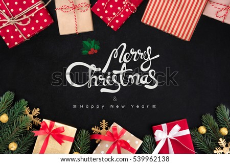 Merry Christmas and Happy New Year text with gift boxes and ornaments on blackboard background
