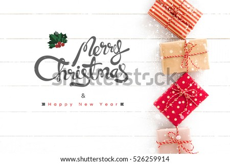 Merry Christmas and Happy New Year text with gift boxes on white wood background, top view