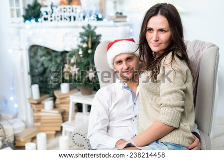 Merry Christmas and Happy New Year. Young beautiful couple in love is sitting on the sofa in festive New Year living room just before the Christmas. Both are happy and hugging