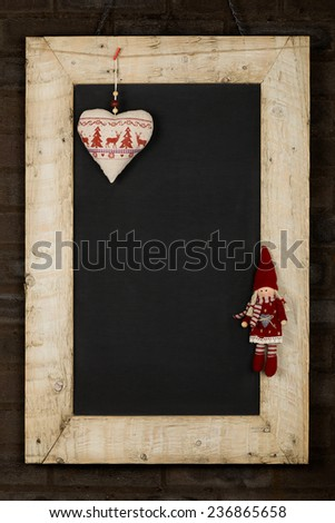 Merry Christmas and Happy New Years chalkboard blackboard heart and puppet decoration restaurant vintage menu design on painted reclaimed wooden frame, dark brown brick wall, copy space
