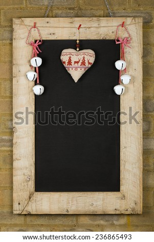 Merry Christmas and Happy New Years chalkboard blackboard tin bells and heart decoration restaurant vintage menu design on painted reclaimed wooden frame, light brown brick wall, copy space