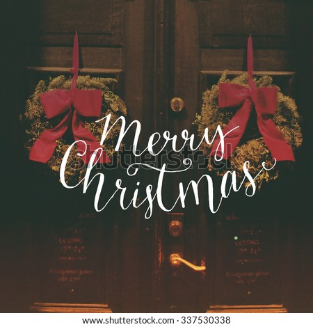Merry Christmas - calligraphy text overlay on filtered photo with decor wreaths on the vintage door. Typography banner for greeting cards and social media content - stock photo