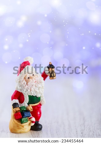 Merry christmas card with Santa Claus figurine. Lights background with space for text. Winter holidays. Xmas theme. - stock photo
