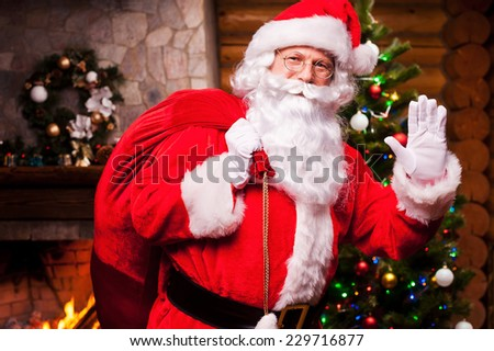 Merry Christmas! Cheerful Santa Claus carrying sack with Christmas presents and waving hand with fireplace and Christmas Tree in the background