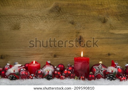 Merry christmas: Classic christmas decoration in red and white with two burning candles on wooden background. - stock photo
