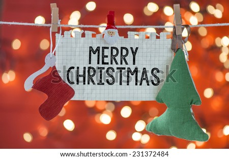 Merry Christmas decoration hanging on rope over red blurred background - stock photo