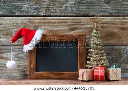 Merry Christmas decorations, empty chalkboard with a red Santa hat, small christmas tree and gifts on a timber background